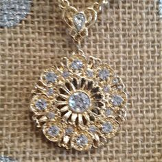 "Faux diamonds in gold round pendant necklace 16"", plus 3"" extension chain. Small faux diamonds surround larger center faux diamond in round, filigree-like gold tone setting. 2028 Jewelry Necklaces"