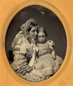 Mother and child. Gorgeous bonnet and dress on mom. Look at that little girl's face!