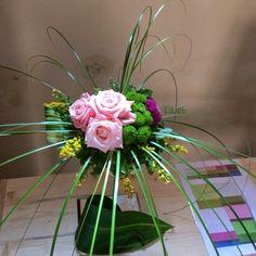 Composizione di rose rosa, solidago, bear grass e bottoncini verdi
