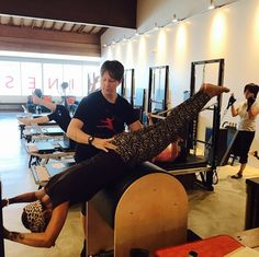"""Coach Kim Smith raising the #intensive and helping clients #challenge their bodies and #push their limits! At the same time, she guides you through #posture for safe and effective #exercises! #seated #Pilates """"V"""" #Stott #chair #grasshopper #barrel lifted #hips #core #work on the #Cadillac #reformer #bicep #curls with a #oneleg #balance #armstoceiling #scissorlegs on the #spinecorrector !!! — at Kinesis."""