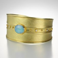 Barbara Heinrich created this exquisite 18k yellow gold, wide oval cuff with an oval, 3.82cttw opal and .20cttw diamonds. @quadrum