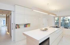 Varný ostrůvek a svítidla nad ním jsou obloženy dřevěnými prkny ve stejném designu, jako je podlaha v obývacím pokoji.