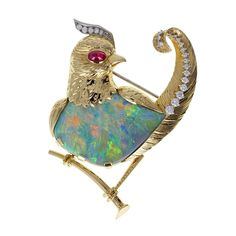 Cartier Opal Ruby Diamond Gold Bird Brooch. A beautiful brooch modeled as a bird perched on a branch. Opal body and textured gold plumage adorned with brilliant-cut diamonds. Single cabochon ruby eye. Signed Cartier circa 1965.   1stdibs.com