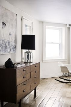 black & silver lamp, wooden chest of drawers, floorboards, white walls