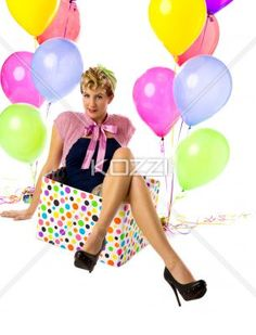 beautiful young woman sitting in a box with balloons on the side. - Portrait of a beautiful young woman sitting in a boxwith balloons on the side, Model: Carrie Galbraith