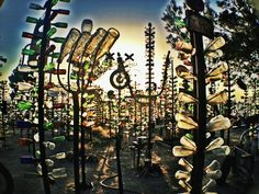 """Bottle Tree Ranch in California """"this bizarre roadside attraction features a forest of metal-and-bottle 'trees'...[the] collection of cobalt blue, amber, green, and milky glass bottles are arranged atop old pipes and rebar that he's welded into sculptures."""""""