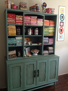 StitcheryDitcheryDock has done wonders with an old china hutch! Repainted, using paints from the megatalented Annie Sloan. No doors above. Instead, all the beautiful supplies show! Like the painted colander also.