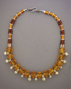 by Anna Holland | Antique Afghani silver amulets are interspersed between amber-colored antique cornerless glass beads from Bohemia from the 1800s, from an area of what used to be the western two-thirds of the Czech Republic. Tiny silver spacers from the Tuareg peoples, and amber and brown glass beads from Indonesia  | Sold