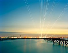 photos of light trails of aircraft over water