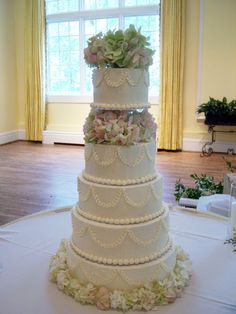 Lovely arrangement of flowers on cake But what about the table??The cake looks so lonely in that big table of nothing. Add greens or tulle, sprinkle some flowers. Use Wedding Bouquets on beds of greens.