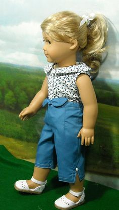 1950s Blue and White Set fits 18 Inch by SugarloafDollClothes. This view shows the medium blue cotton capris with the floral shirt that has medium blue accents. Tiny white buttons flank the little faux tie at the waist and also top the slits on the pant leg sides.
