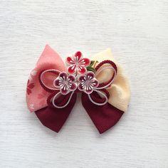 ✤ご覧頂きありがとうございます✤ ちりめん生地のりぼん(ポリエステル)に、正方形の小さな布を折りたたんで作るつまみ細工で作成した正絹の梅、3輪をUピンで添えました。りぼんは縦約12cm、横約14cmでボリューム感があります。梅一輪の花の大きさは約3cmで...