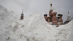 Za haldami sněhu na Rudém náměstí je vidět Spasská věž (vlevo) a chrám Vasila Blaženého.
