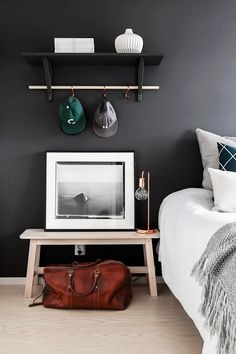 Bedroom with dark walls, white bedding, black and white photography and a wooden table