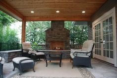 Covered patio with fireplace. This is exactly what I want my back porch to look like