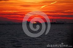 Photo taken at sunset on the lagoon of Venice Italy. In the picture it looks like the clouds over the water and a part of the city have caught fire. Horizon, partially hidden, you see a small slice of the sun for a moment before it disappears altogether.