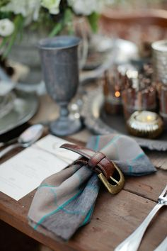 Wonderful country tablesetting in blue and grey plad. Pewter stemware, leather belt napkin ties & woodsy decor make this easy on your eyes.
