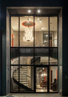 the façade maximizes transparency to reveal the original structures, like the spiral staircase and chandelier.