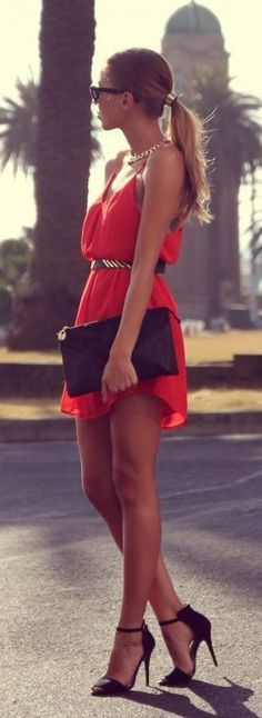 Holiday red dress with black & gold belt, black clutch, necklace and sunglasses. Ponytail hairstyle.