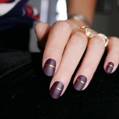 Purple matte manicure with an elegant gilded ribbon through the center