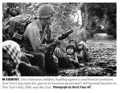 Dos niños se refugian junto a un paracaidista con un lanzagranadas.
