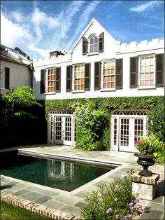 Charming Charleston home with paneled windows, black shutters and an ivy-covered facade by the pool.