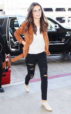 Emily Ratajkowski wears a white t-shirt, suede motorcycle jacket, distressed black skinny jeans, neutral oxfords, and round glasses