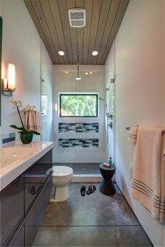 This modern bathroom features a wood ceiling and a glass-enclosed rainfall shower.