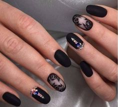 Wonderful looking rose nail art design in black. The black color gives the rose a very strong look and also the addition of the colorful embellishments give life to the otherwise all back design. The matte black polish is also perfect for this design.