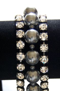 From the Dark Elegance Collection- The GRETA Bracelet by Shandy Nicole Designs. This bracelet really sparkles! Two strands of Austrian crystal rhinestones set in hematite metal surrounding a strand of dark gray Swarovski pearls.