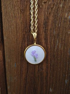 "A small, simple, hand embroidered necklace featuring a calming herb, Lavender.    - Lead and nickel free!  - This setting is gold tone and 30mm diameter - slightly larger than a quarter.  - Chain (gold setting) is about 18"" with clasp."
