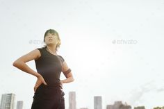 Fitness woman standing with her hands on hips and looking away by jacoblund. Outdoor shot of fitness woman standing with her hands on hips and looking away. Female runner taking break from outdo...