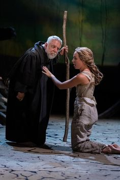 Prospero leaning down to the listen to his daughter, Miranda