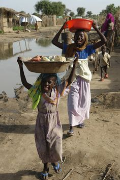 Two girls smile after fetching water at Ardamata IDP camp, near Sudan, West Darfur, El Geneina, August 2006 (Photo:WFP/ Emilia Casella)