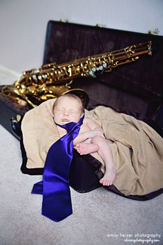 baby in his daddy's saxophone case with purple tie