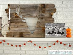 Keep your mantel simple with a stacked mini pumpkin arrangement and a rustic garland.