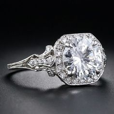 Shoulder view: 2.17 Carat 'D' color diamond Edwardian style engagement ring at Lang Antiques. A superb 2.17 carat round brilliant-cut diamond - accompanied by a GIA Gem Trade Laboratory grading report stating D color, VS2 clarity- is framed by small sparkling accent diamonds atop a fancy scroll motif gallery and openwork foliate motif diamond-set shoulders.  Via Diamonds in the Library.