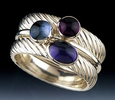 The Blues by Donald Pekarek. Three sterling silver and 14K rings set with (top to bottom) amethyst, London blue topaz and iolite *cabochons:cabochon*. Center ring is 14k, and 14k bezels hold the gems on the wide silver rings.
