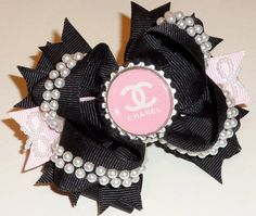 Chanel inspired Couture triple stacked black with faux pearls Boutique Hair Bow and pink Chanel/CC bottlecap embellishment. $9.99, via Etsy.