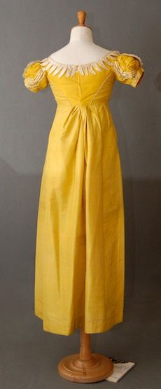 Yellow Silk Dress c 1810 Description the empire bodice with curving cream satin decoration, the edges rouleau trimmed, the front, back and sleeves with bands of cream satin and blonde lace, original neck drawstring, shoulder to back hem 51 in or 1.3 m