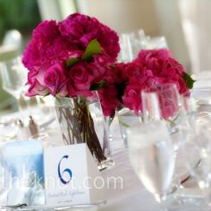 Short, square vases filled with roses and hydrangeas topped some of the reception tables, coordinating with the bridal bouquet. Blue table numbers tied in the full color scheme.
