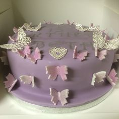 Purple and silver butterfly cake   This cake was made using butterfly cutters for the sugarpaste butterflies and cake lace for the lace hearts and butterflies. Stencils and silver dust were used for the writing