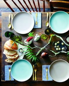 Fun, Funky tablescape with mixed plates and lichen covered branches.