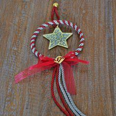 Χειροποίητο γούρι επίχρυσο αστέρι με γκρι σμάλτο σε χειροποίητο στεφανάκι από δίχρωμο κορδόνι κόκκινο και γκρ