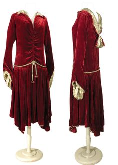 Dress, Paul Poiret, ca. mid-1920s. Medieval-style dropped peaked waistline girded by plaited metallic gold cord, ending in velvet pompom. Set-in fluted sleeves with cuff points revealing gold lamé lining. Bodice draped to center front seam, deep V-neckline front & back, modified gold lamé shawl collar overlapping to faux bow at back. Gathered skirt w/handkerchief hem piped in gold lamé.
