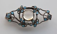 Jessie M. King (Scottish). Liberty & Co brooch. Silver, gold, enamel and moonstone, c. 1900. H: 1.6 cm (0.63 in)  W: 3.3 cm (1.3 in). Fitted case. Sold by Tadema Gallery. View 2.