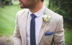 Groom in round collar white shirt with navy & white polka dot tie & pocket square - Image by Guy Collier - Tipi Wedding With Bridesmaids In Blue Ghost Dresses With Bride In Gown From The Bespoke Wardrobe With Groom In Relaxed Jacket And Trousers