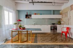 A colourful kitchen in Barcelona. Mint green backsplash and light blue wall contrast with the old stone floor with decorative patterns. From Home DSGN