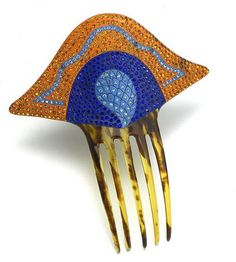 English Art deco comb is painted orange with two colors of blue. Rhinestones match the paint. The decoration was painted on faux tortoiseshell. circa 1920.
