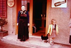 Austrian lady in traditional dress stands outside hostel with Peggy and cat in Egg, Austria, 1962